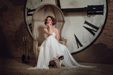 A smiling girl in a wedding dress in strange chair.