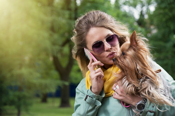 Happy women talking cell phone and kissing her dog