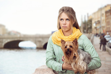 Sad girl with little dog on the bank of the river