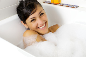 Smiling beautiful young woman in bathtub full of foam
