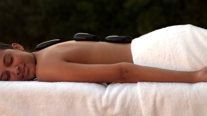 Calm brunette enjoying a hot stone massage