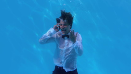 Cheering businessman underwater in pool talking on smartphone
