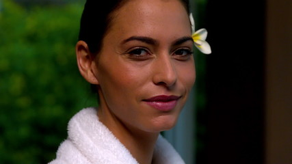 Beautiful brunette in bathrobe smiling at camera at the spa