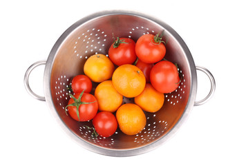 Tomatoes and mandarins in colander.