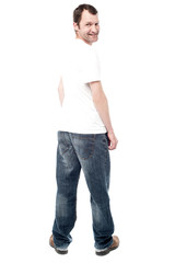 Handsome man in jeans standing back
