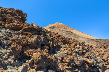 Peak of Teide volcano behind volcanic rocks in Tenerife