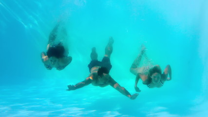 Friends swimming underwater in pool together