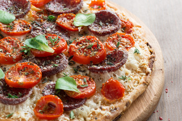 Italian pizza with salami and tomatoes, close-up