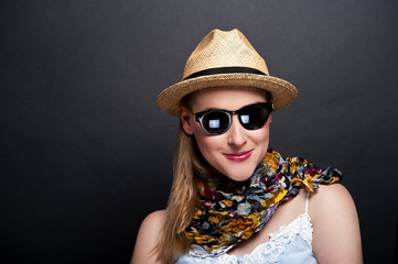 woman in hat and sunglasses over dark background
