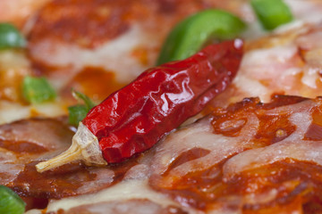 Close-up of red hot peppers on pizza with sausages.