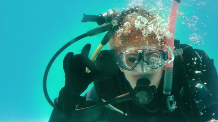 Woman in scuba gear looking at camera underwater making ok sign