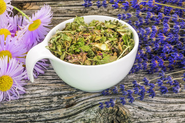 Natural herbal tea with meadow flowers around on old wood