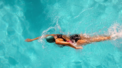 Fit female swimmer doing the front stroke in the swimming pool