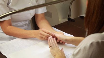 Nail technician examining customers hands