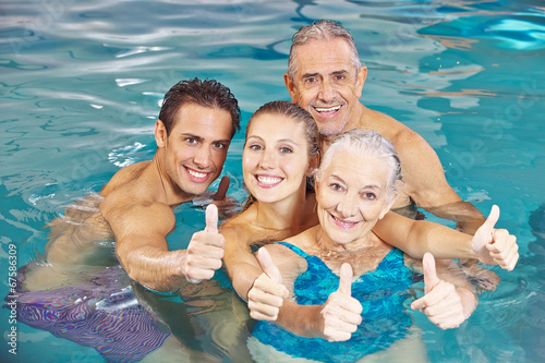 Familie im Schwimmbad hält Daumen hoch - 67586309