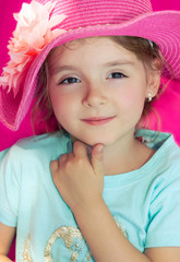 Little girl closeup in pink summer hat. Beautiful smiling face.