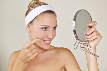 Attraktive Frau betrachtet sich im Spiegel