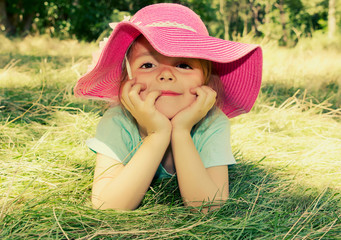 Little girl lying on grass outdoor. Smiling girl face closeup.