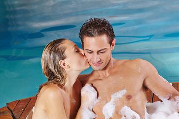 Frau küsst Mann im Whirlpool im Spa