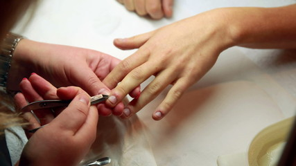 Nail technician removing cuticles from customers nails