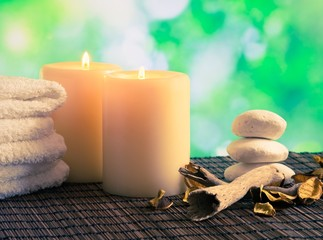 Spa massage border with towel stacked, candles and stone