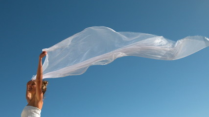 Carefree blonde holding scarf up blowing in the wind