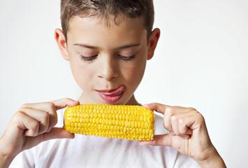 Niño comiendo maíz dulce