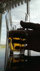 Glass of beer in male hand. Silhouette above a bright window