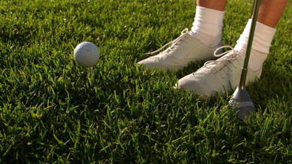 Golf ball falling beside lady golfers feet and club