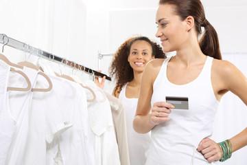 Kobiety w sklepie odzieżowym płaca za zakupy karta kredytową.