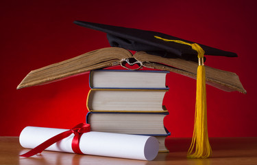 mortarboard and graduation scroll on a stack of  book