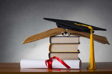 mortarboard and graduation scroll on a stack of battered book
