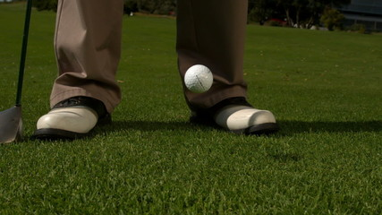 Golf ball falling beside golfers feet and club