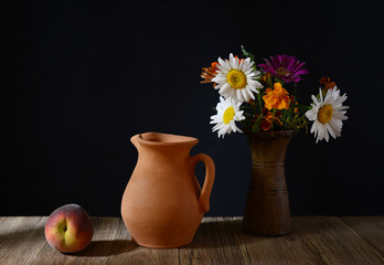 Ceramic carafe, peaches and flowers in a vase