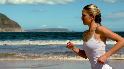 Fit blonde jogging on the beach