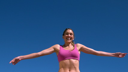 Fit blonde smiling and jumping up on sunny day