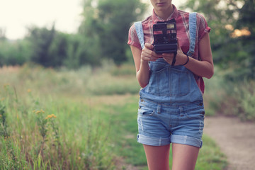Hipster girl posing with instant camera