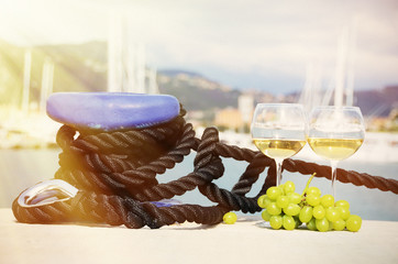 Pair of wineglasses and grapes against yachts in La Spezia, Ital
