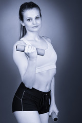 Young fitness woman lifting dumbbells