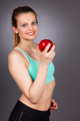 Portrait of  happy beautiful woman in fitness wear holding a red