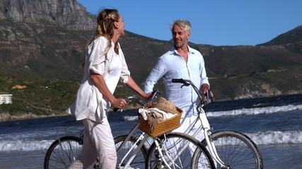 Carefree couple walking on the beach with their bikes