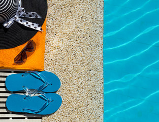 Flip Flop, towel, hat on pool edge with surface of water