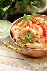 fried prawns with chilli in a copper pan, Indian style