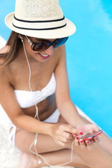 Beautiful girl listening to music in the swimming pool.