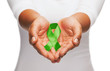 hands holding green awareness ribbon