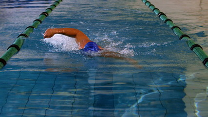 Fit swimmer doing the front stroke in swimming pool