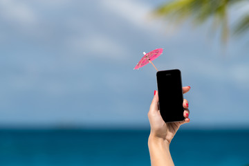 Woman hand showing mobile phone and cocktail umbrella