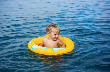 Little boy in water on rubber ring