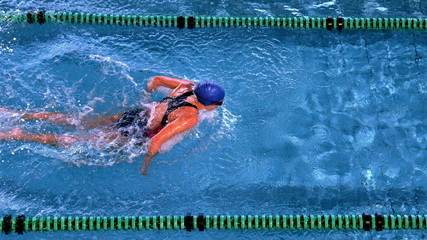 Fit female swimmer doing the butterfly stroke in swimming pool