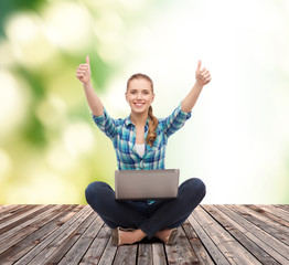 smiling woman with laptop and showing thumbs up